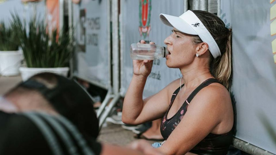 Woman drinking water after finishing a race