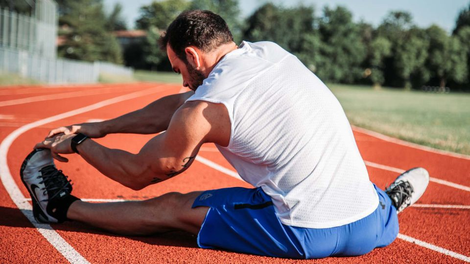 Runner stretching on the track