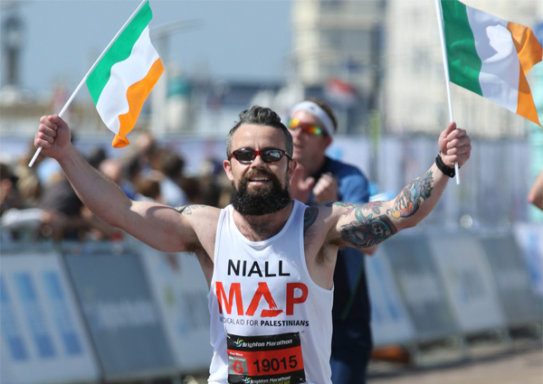 Man running in MAP vest with irish flags