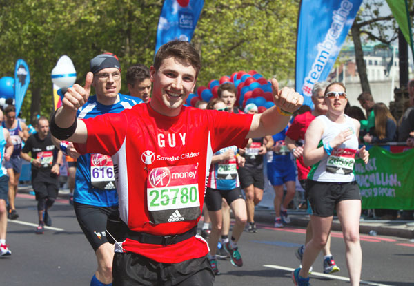 Happy runner gives thumbs up in Save The Children red vest