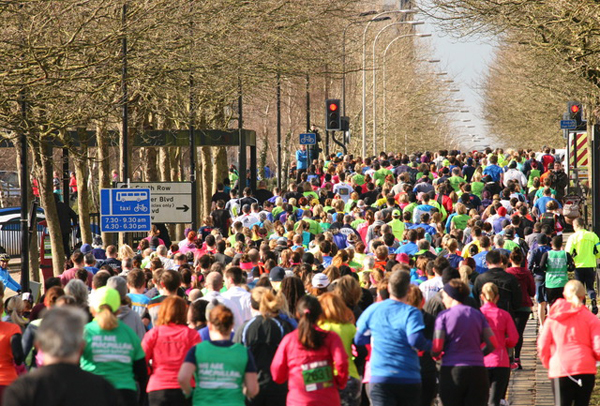 great shot of massed runners on MK tree-lined boulevard