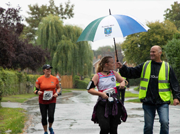 Man with umbrella shelters runner in race