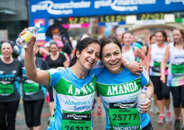 Two delighted women in charity vests after Great Manchester Run