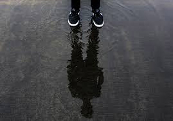 Foot and ankle shot of runner with full shadow in puddle